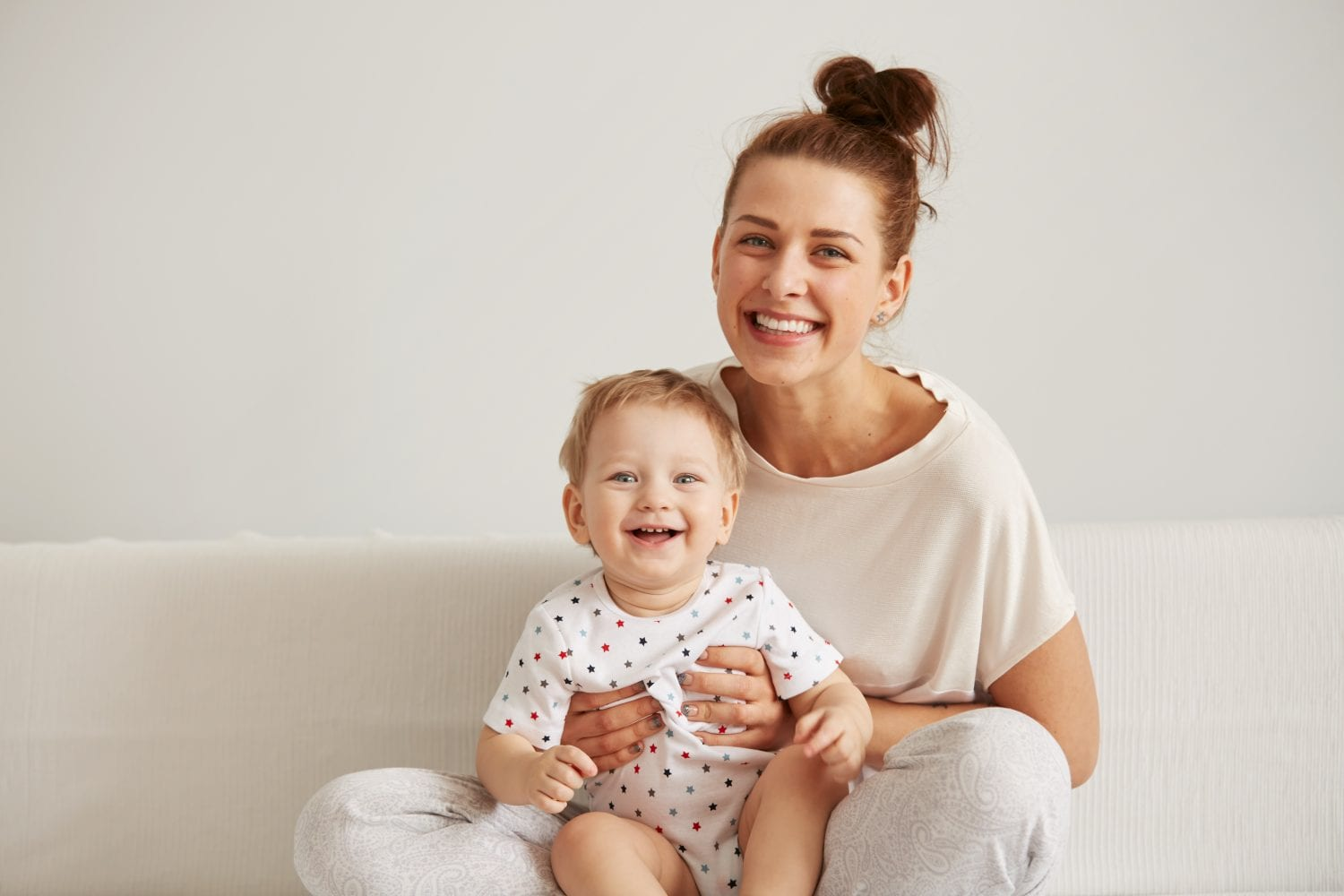 Charming brunette woman playing with her baby while sitting on a bed in her apartment at the weekend together, lazy morning, warm and cozy scene. Selective focus